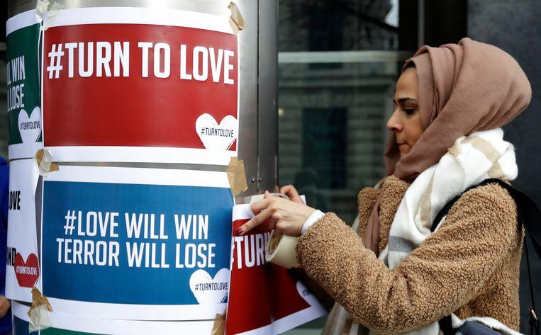Demonstrant hangt bij het Nieuw-Zeelandhuis in Londen pamfletten op tegen de moord op moslims in Nieuw-Zeeland.  Beeld AP Photo/Kirsty Wigglesworth