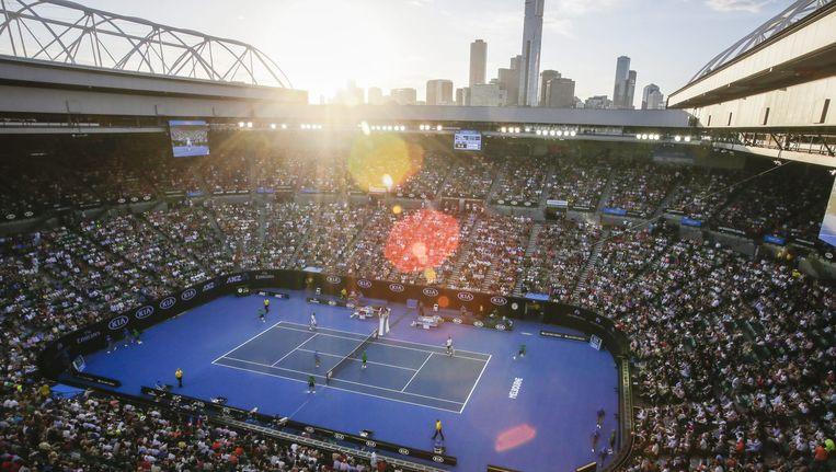 Een bomvolle Rod Laver Arena met in de achtergrond de skyline van Melbourne tijdens het Australian Open Grand Slam-toernooi. Beeld null