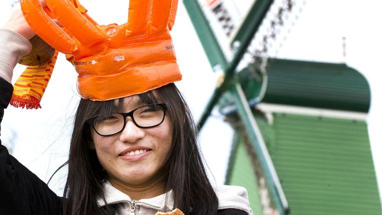 Een Japanse toeriste poseert op de Zaanse Schans voor een versierde molen Beeld anp