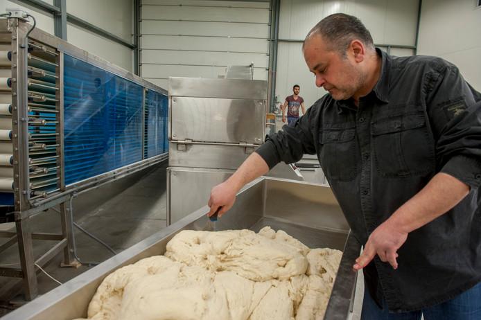 Ibrahim el Yamani conroleert het deeg voor de broodjes die hij maakt.