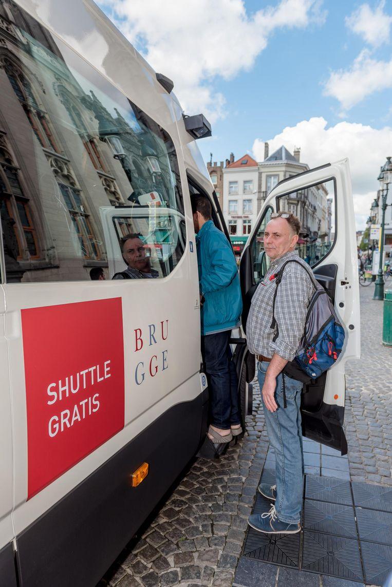 Een passagier stapt op het gratis shuttlebusje.