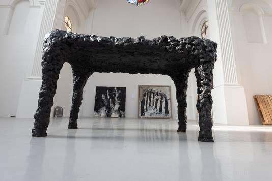 De twee uit de brand geredde doeken van Armando, zichtbaar onder één van zijn karakteristieke sculpturen.