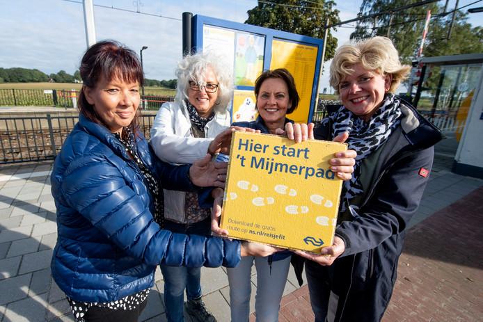 Jakelien, Mariska, Ina en Magda (vanaf links) plaatsen de tegel van het Mijmerpad bij het informatiebord van het station in Holten.