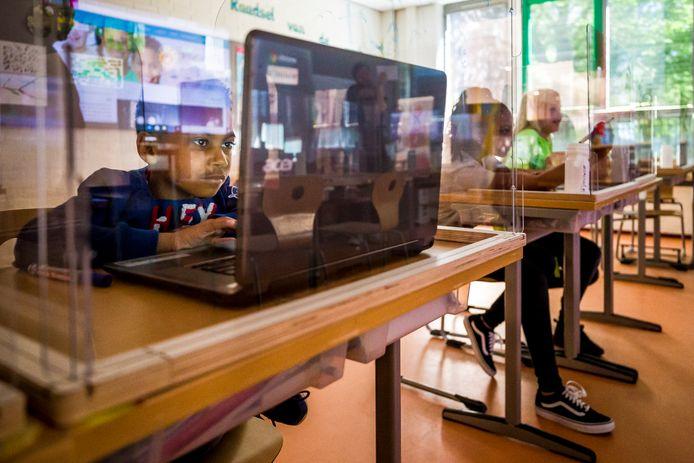 Plexiglas hokjes om de schoolbanken bij kindcentrum De Springplank. Victor is aan het werken op z'n laptop.
