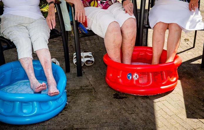 Bewoners van een verzorgingshuis in Zeist houden hun hoofd en voeten koel tijdens de tropische hitte.