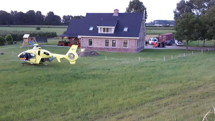 De traumahelikopter landt naast de woning aan de Lekdijk in Lopik waar het vermoedelijke familiedrama zich heeft afgespeeld.
