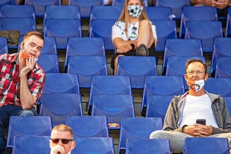 Supporters van de club kijken naar de training met mondkapjes op.   Beeld