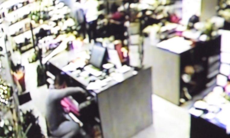 De dief rooft de kassa leeg, terwijl twee kompanen de winkeliers en klanten afleiden.