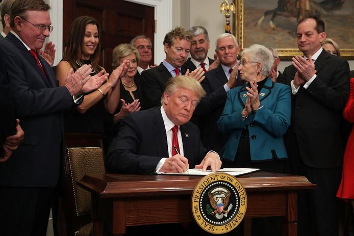 President Donald Trump tekent het presidentieel bevel.