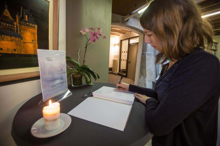 Een inwoonster tekent het rouwregister.