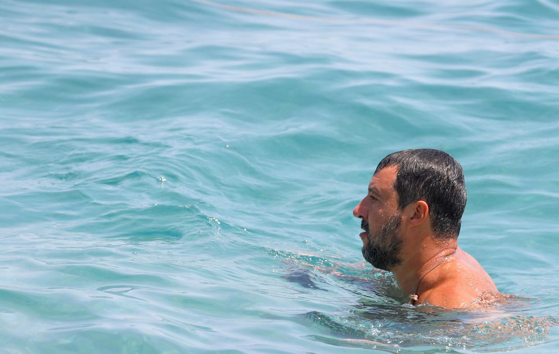 Matteo Salvini neemt een duik na wat foto's te hebben genomen met zijn fans bij het strand van het Sicilische Taormina.