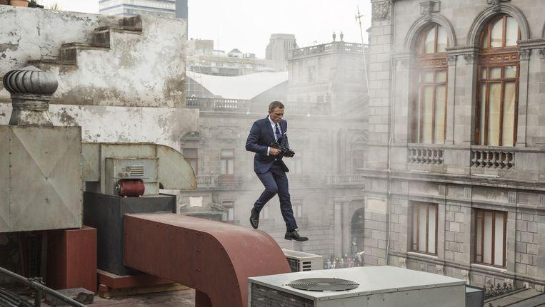 James Bond (Daniel Craig) zet de achtervolging in over de daken van Mexico-stad. Beeld Jonathan Olley
