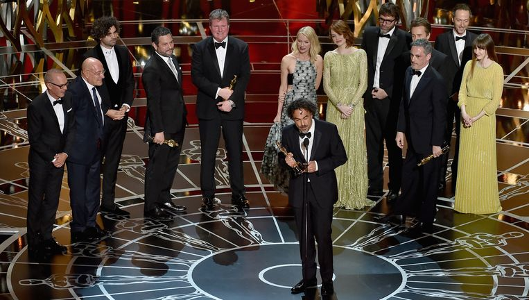 Regisseur Alejandro González Iñárritu neemt, omringd door de cast en crew van Birdman, de Oscar voor beste film in ontvangst Beeld Getty Images