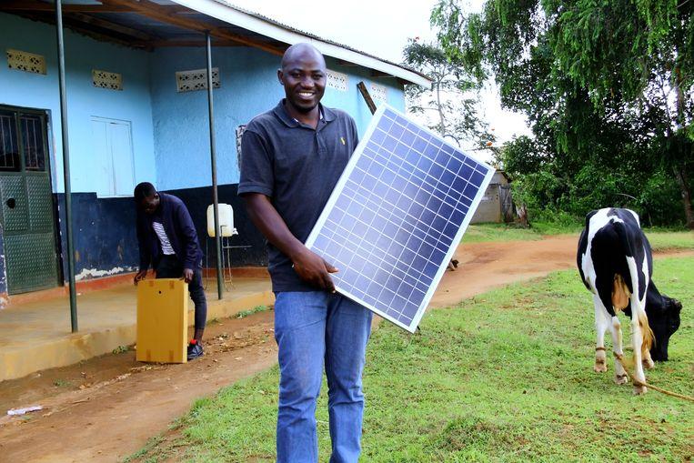 Een Oegandees met een Rural Spark thuissysteem. Beeld Ian David Luyinda