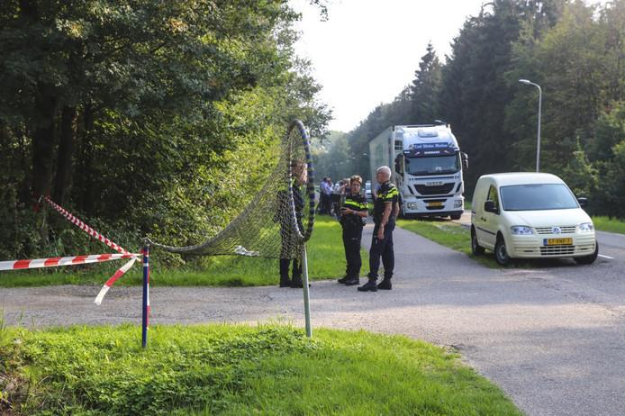 Agenten zoeken naar de vrachtwagenchauffeur, met op de achtergrond de verlaten truck.