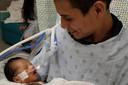 De kleine Yadiel in de armen van zijn vader.