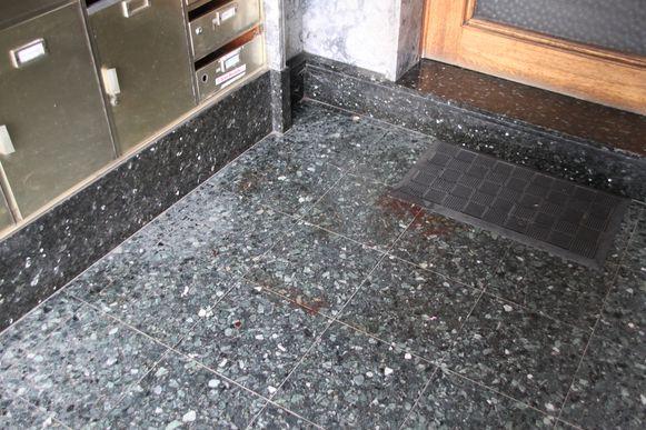 Bloedsporen in het portaal van een appartementsgebouw aan de overkant van de straat.