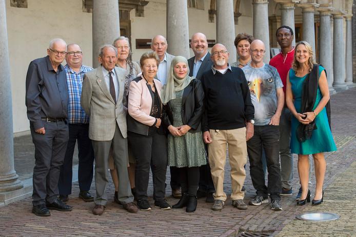 Twaalf van de hoofdpersonen in het boek Goed Volk poseren samen met initiator Anita van der Helm (geheel rechts).