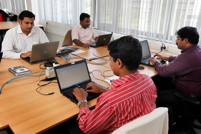 Ict-specialisten uit India aan het werk in het hoofdkantoor van uitgeverij Wegener in Apeldoorn.