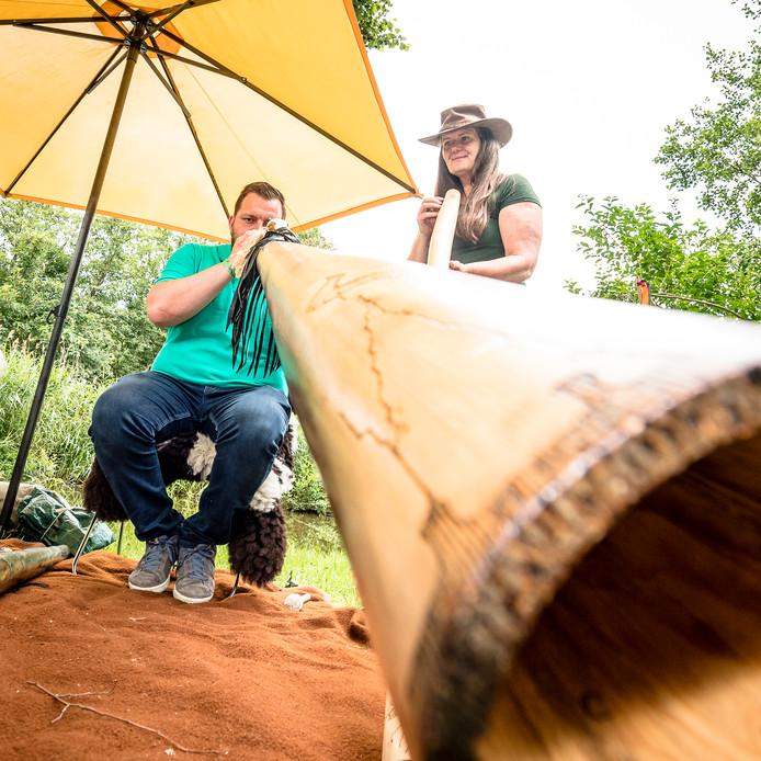 De verslaggever probeert didgeridoo te spelen.
