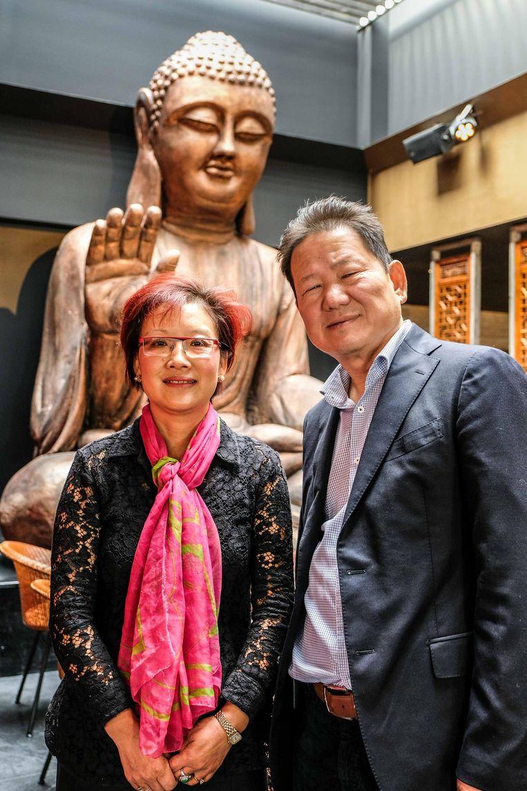 Eigenaars Wu Chang Ying en Peh-Fo Pak bij het vier meter grote boeddhabeeld, de blikvanger in het restaurant.