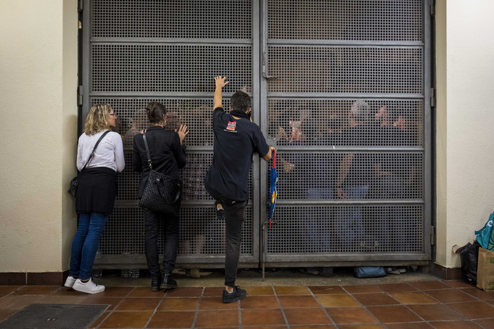 Buiten bewaken mensen het stembureau Escola Cervantes. Inwoners van Barcelona brachten hun stem uit over een omstreden referendum over onafhankelijkheid van Catalonië.
