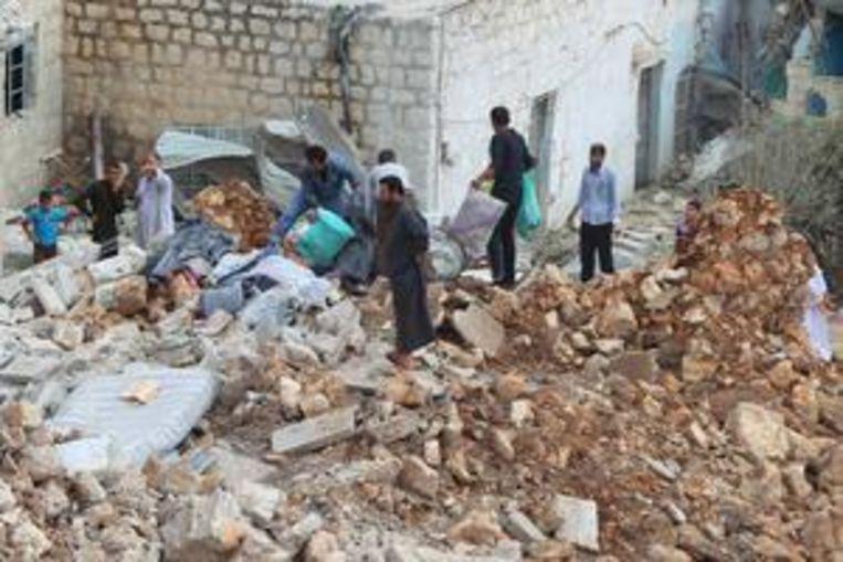 Burgers in het Syrische dorp Datat Izza bekijken de schade na een Russische luchtaanval woensdag.