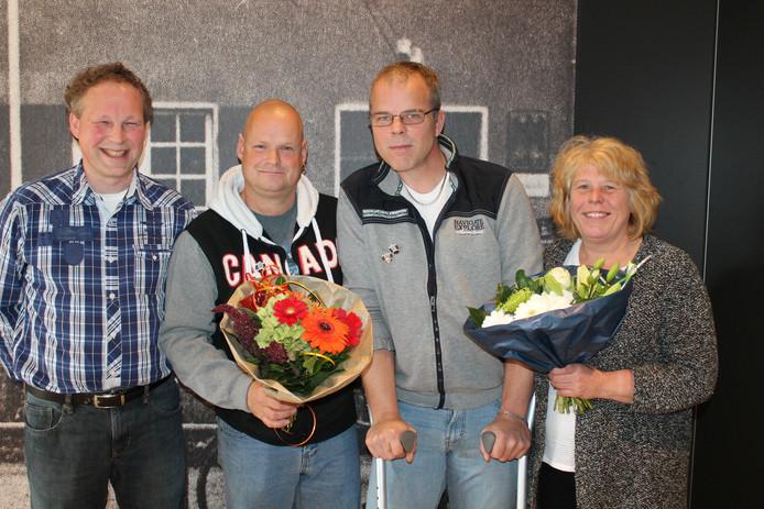 De beide jubilarissen Peter Oud (met krukken) en Jan Bijkerk (met bloemen) nemen de felicitaties in ontvangst van voorzitter Andre Westenbroek. Geheel rechts Femie Cath, de echtgenote van Peter Oud.