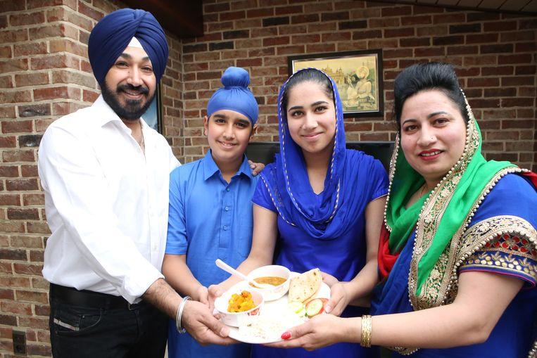 Het gezin stelt één van de typische maaltijden voor.