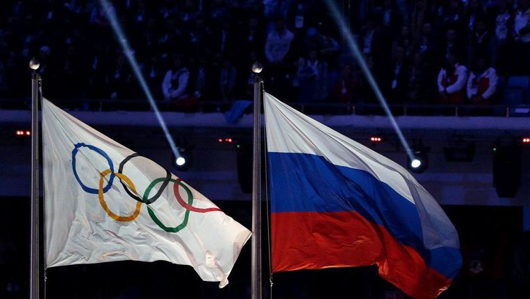 De Russische vlag naast de Olympische vlag tijdens de Winterspelen in Sotsji in februari 2014. Beeld AP