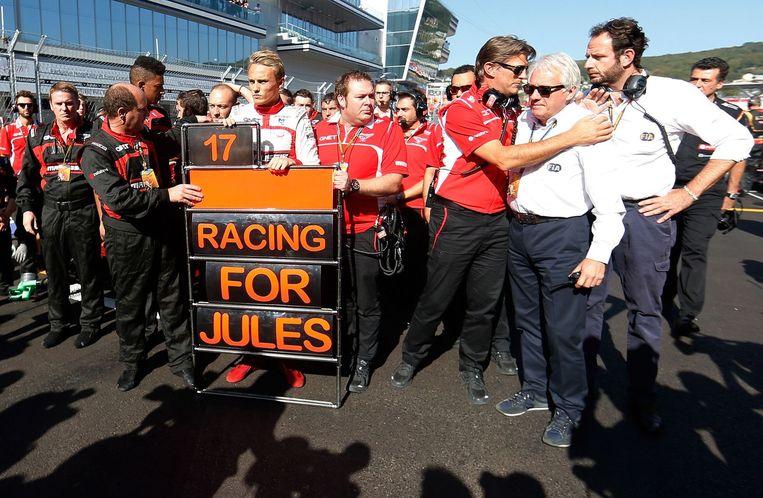 Bianchi's Marussia teamleden staan stil bij het ongeluk. Beeld afp