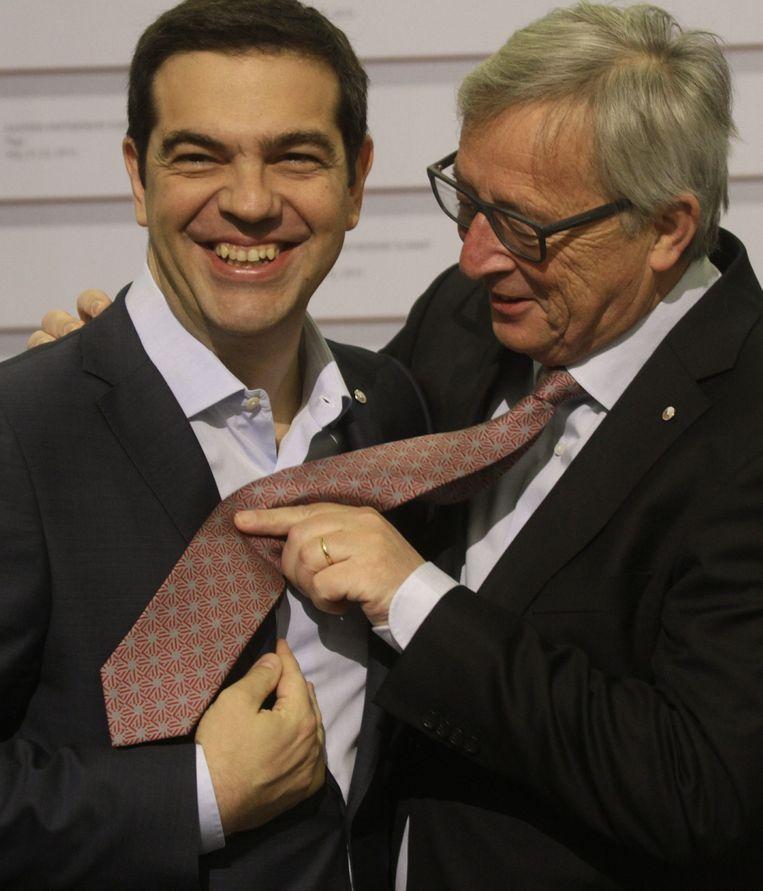 Europese Commissie-voorzitter Jean Clauda Juncker maakt een grapje bij de Griekse premier Alexios Tsipras, die zonder das aankwam. Beeld epa