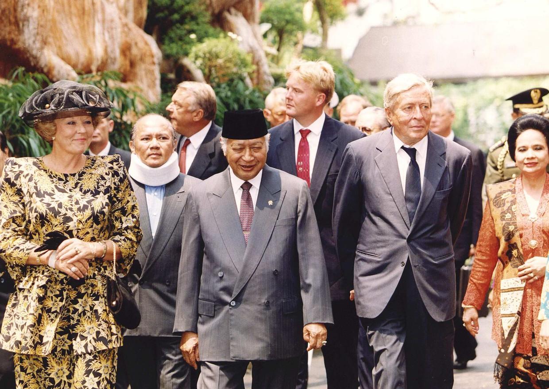 De Indonesische president Soeharto (midden) brengt zijn gasten via de tuin naar de gastenverblijven van het Merdeka-paleis. Beeld ANP