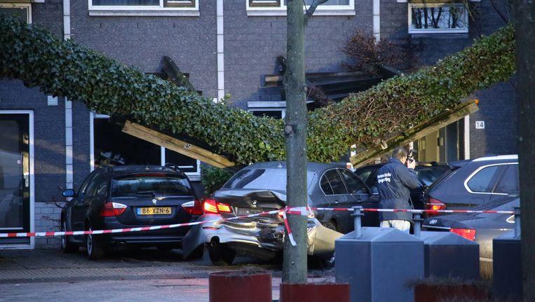 Bij de actie van het arrestatieteam in de Knokkestraat werd een pergola omver gereden en werden meerdere geparkeerde auto's geraakt. Beeld anp