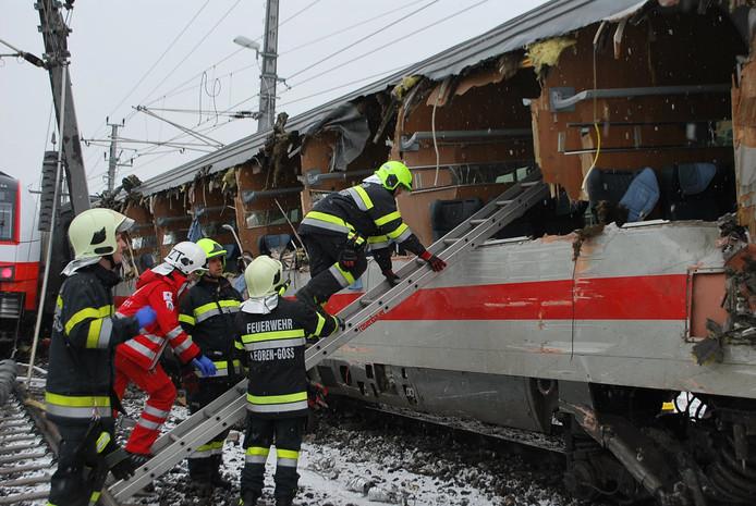 Reddingswerkers aan de slag in de beschadigde trein