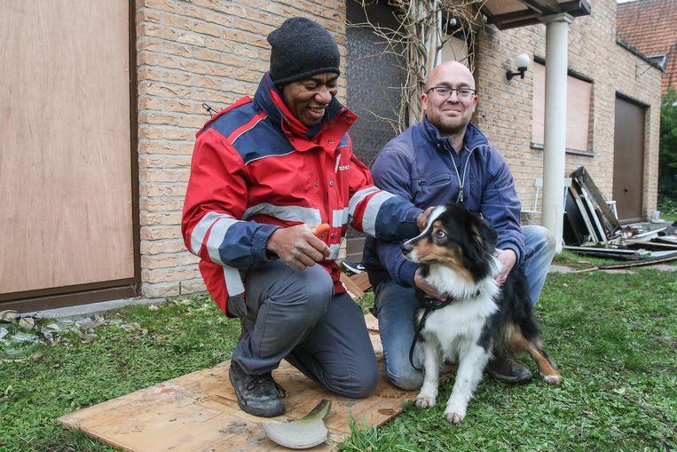 Postbode Serge Nsinga en bewoner Philip Bernard met zijn hond Fanny.