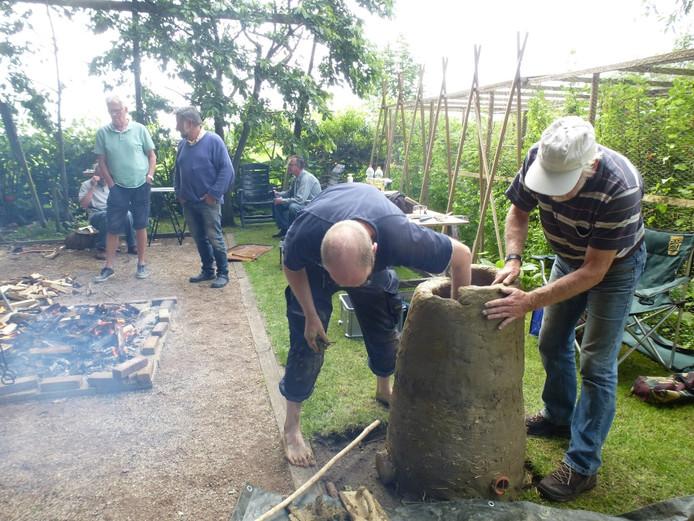 De bouw van een leemoven. Links het vuur waarin de klappersteen wordt geroost.