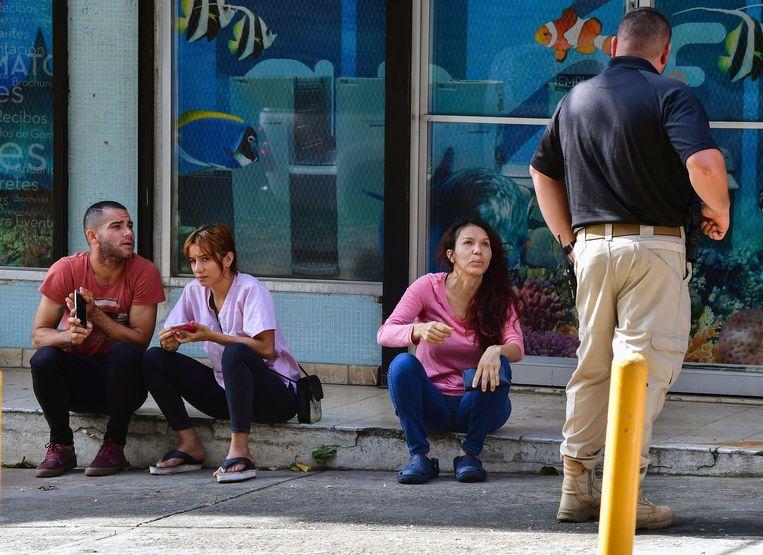 Drie mensen die verdacht worden van het smokkelen van migranten worden in de gaten gehouden door een agent (staand) in Panama.