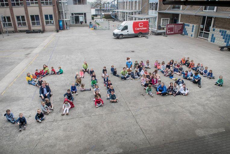 Op de speelplaats van de Broederschool vormden de kinderen het woord 'samen'.
