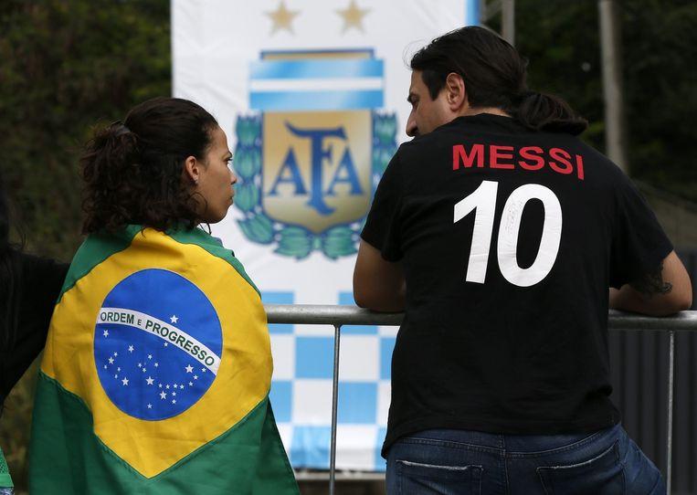 Een Braziliaanse en een Argentijnse voetbalfan bij het trainingscomplex van Argentinië Beeld AFP
