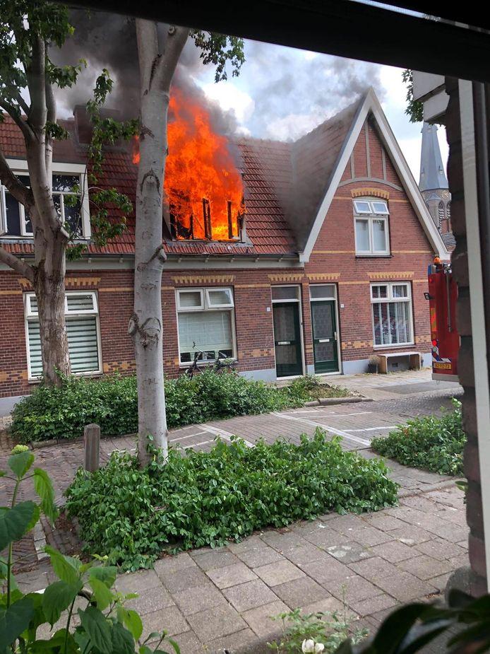 De vlammen slaan uit het dak van de woning aan de Almelose Noorderstraat.  De brandweer is op dat moment nog onderweg.