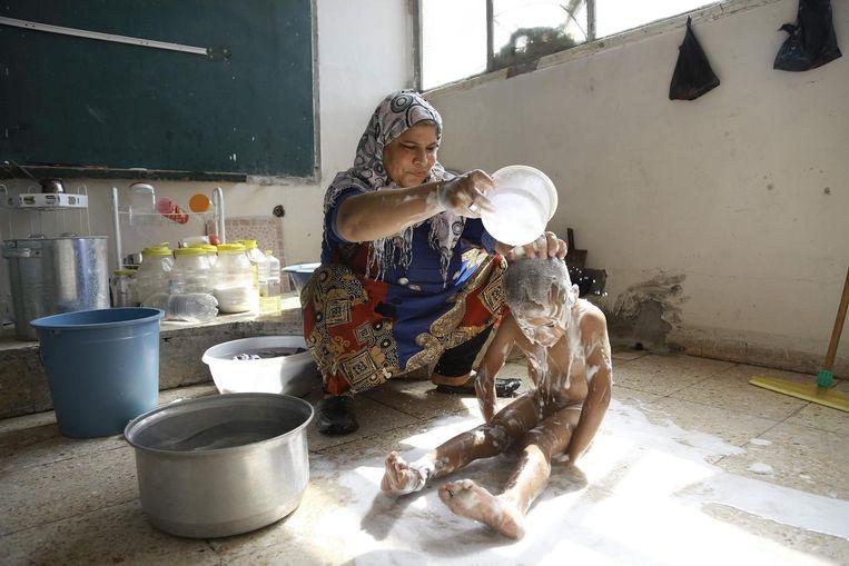Een Syrische vrouw doucht haar kind in een opvangkamp in Qamishli, in Syrië. Beeld null
