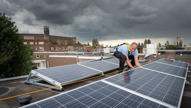 Op huurwoningen aan het Harmoniehof (Zuid) worden zonnepanelen geplaatst. Beeld Mats van Soolingen
