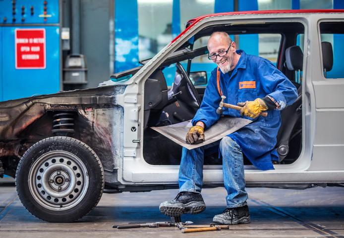 Bertus Fruytier is bezig met het plaatwerk van een oude Volkswagen Golf en geniet er met volle teugen van.