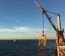 De installatie van de fundering van een windmolen op zee