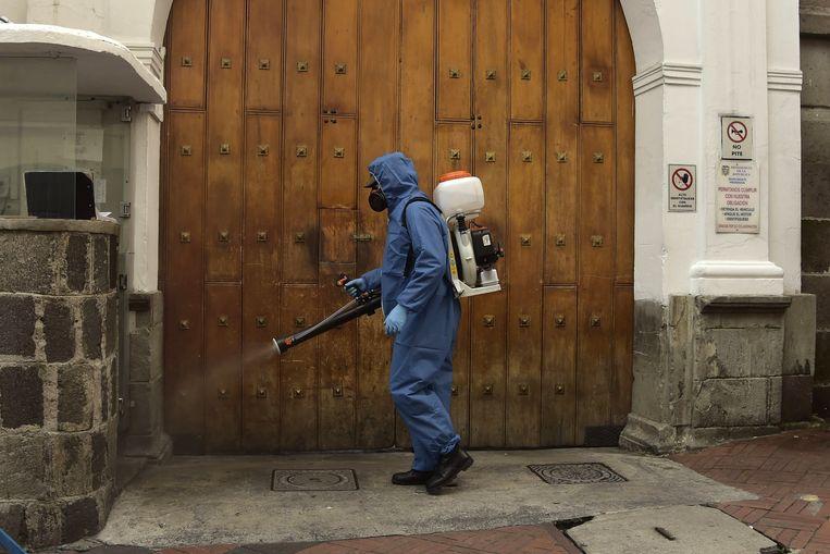 Een man desinfecteert de straten van Quito in Ecuador.