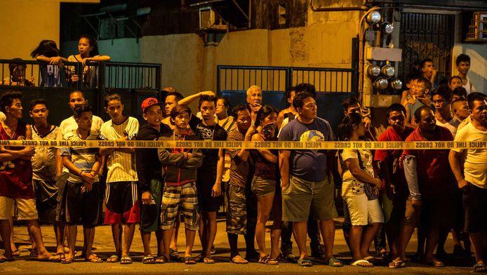 Buurtbewoners staan achter een politielint te kijken naar politieonderzoek