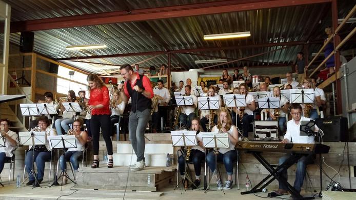 Fanfare Concordia met vocalisten Lisa van Nunen en Fons van Heesch jr in de loods van aannemersbedrijf Van Nunen