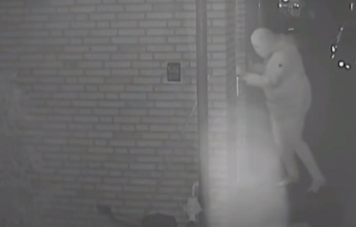Een screenshot uit de uitzending van Opsporing Verzocht. Een derde gemaskerde overvaller probeert de woning aan de Thorbeckestraat binnen te komen.