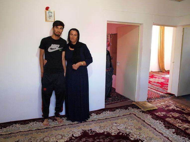 Iran Rasulzadeh met een van haar drie zoons. Ze verloor haar man bij de aanslag, boven hen hangt zijn portret als jonge man.  Beeld Judit Neurink